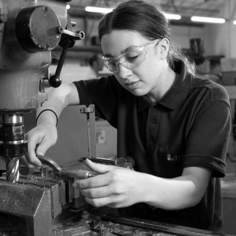 Engineering apprentice inspecting a machined part