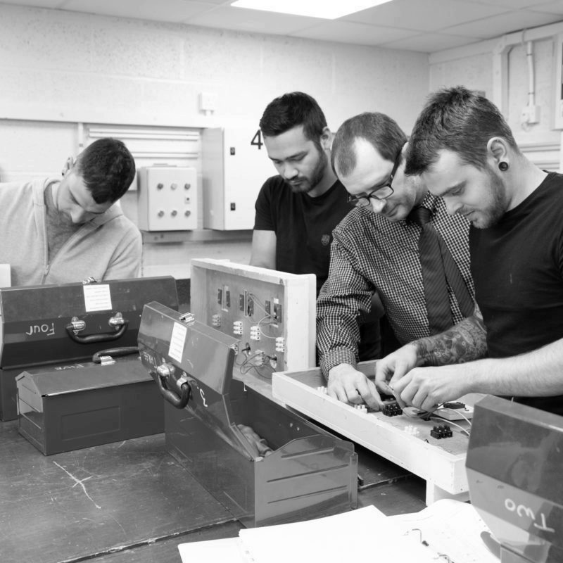 Engineers on training course creating electrical circuits