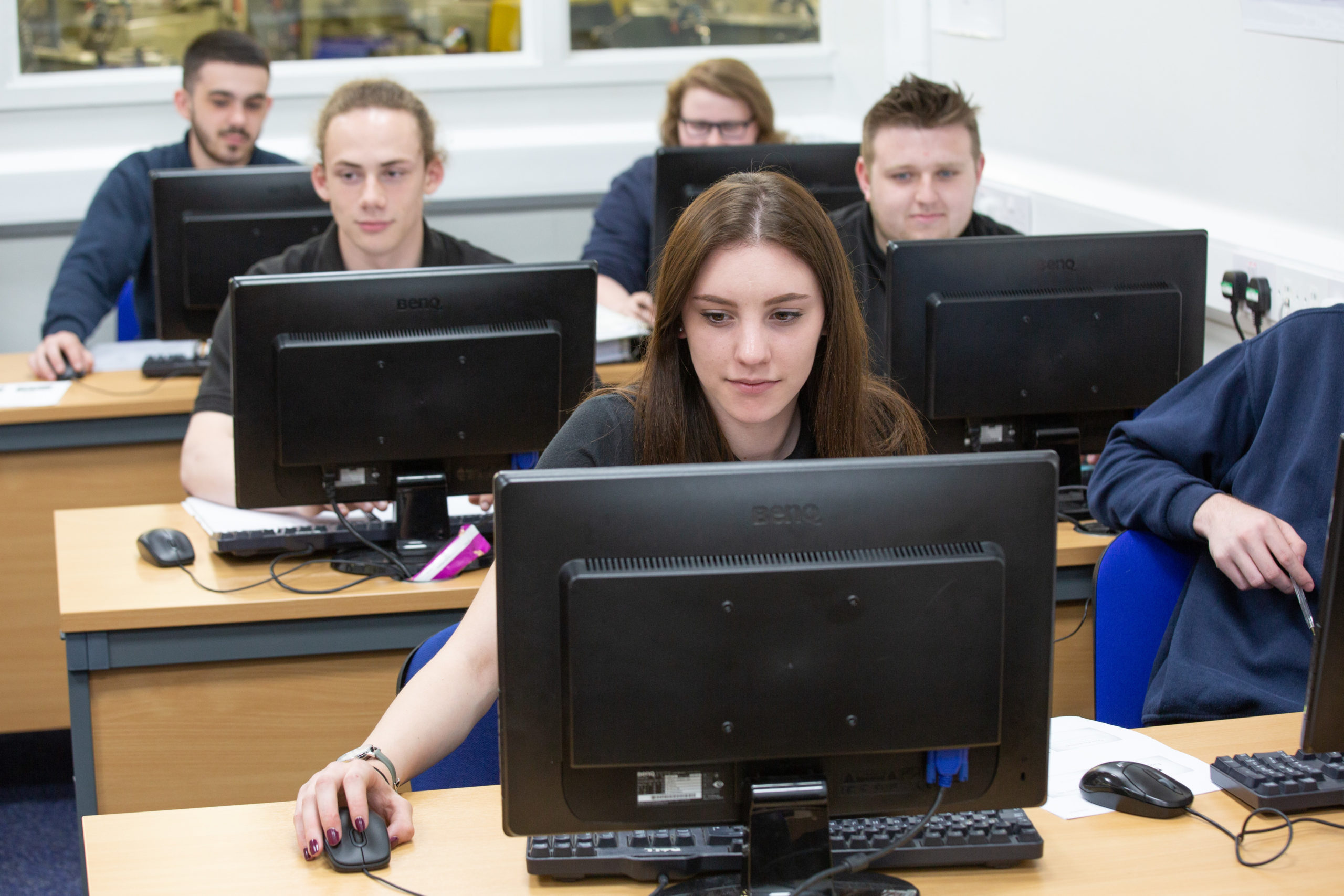 Apprentices using computers doing coursework