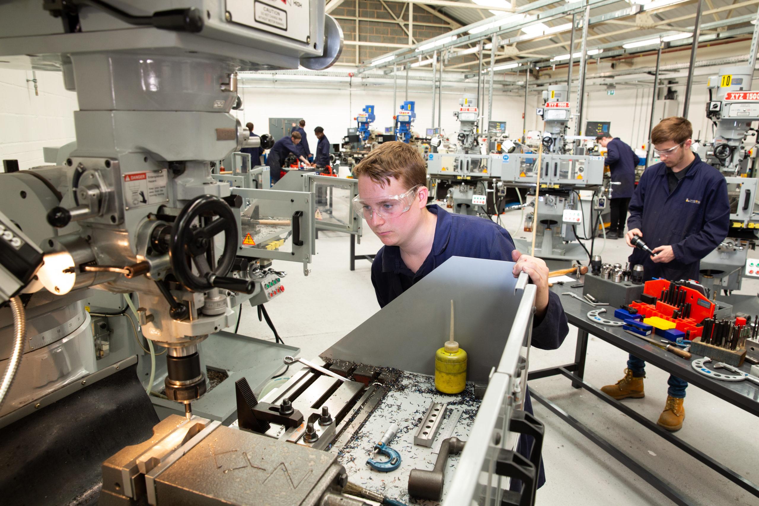 Engineering apprentice using milling machine