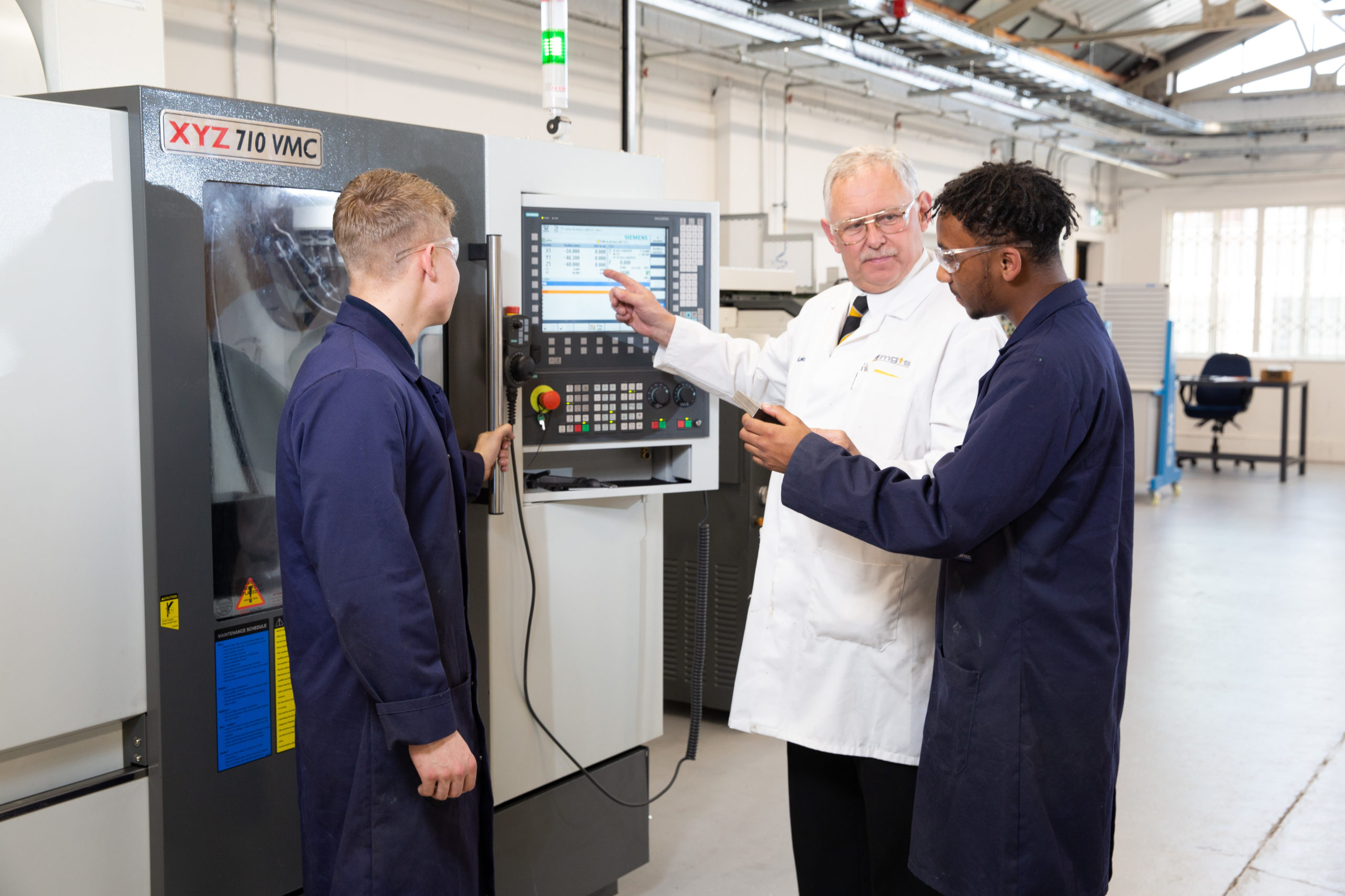 Teacher showing two engineering apprentices how to use machinery