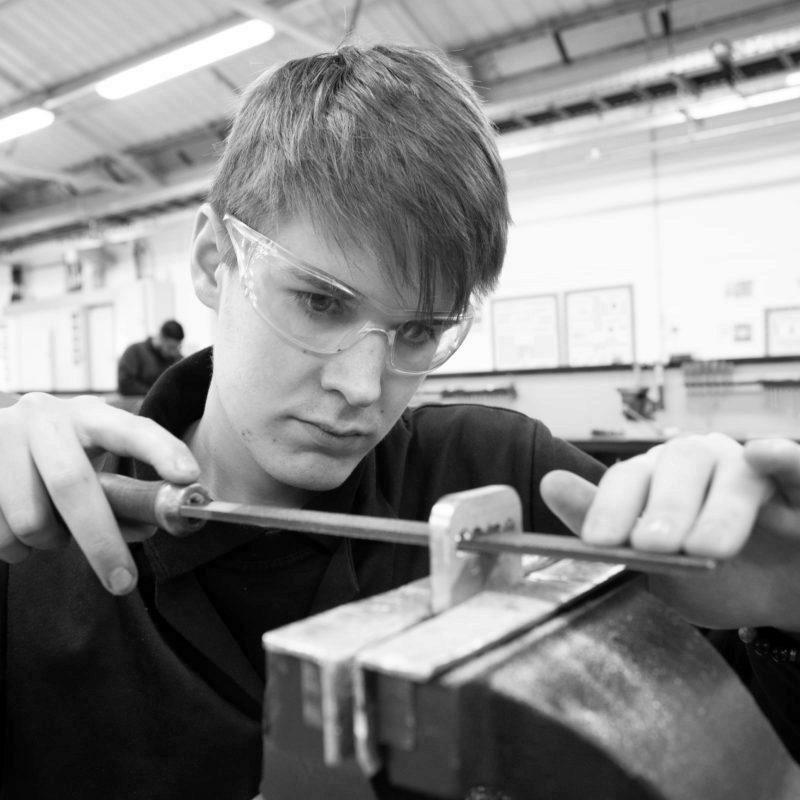 Machinist apprentice hand filing part