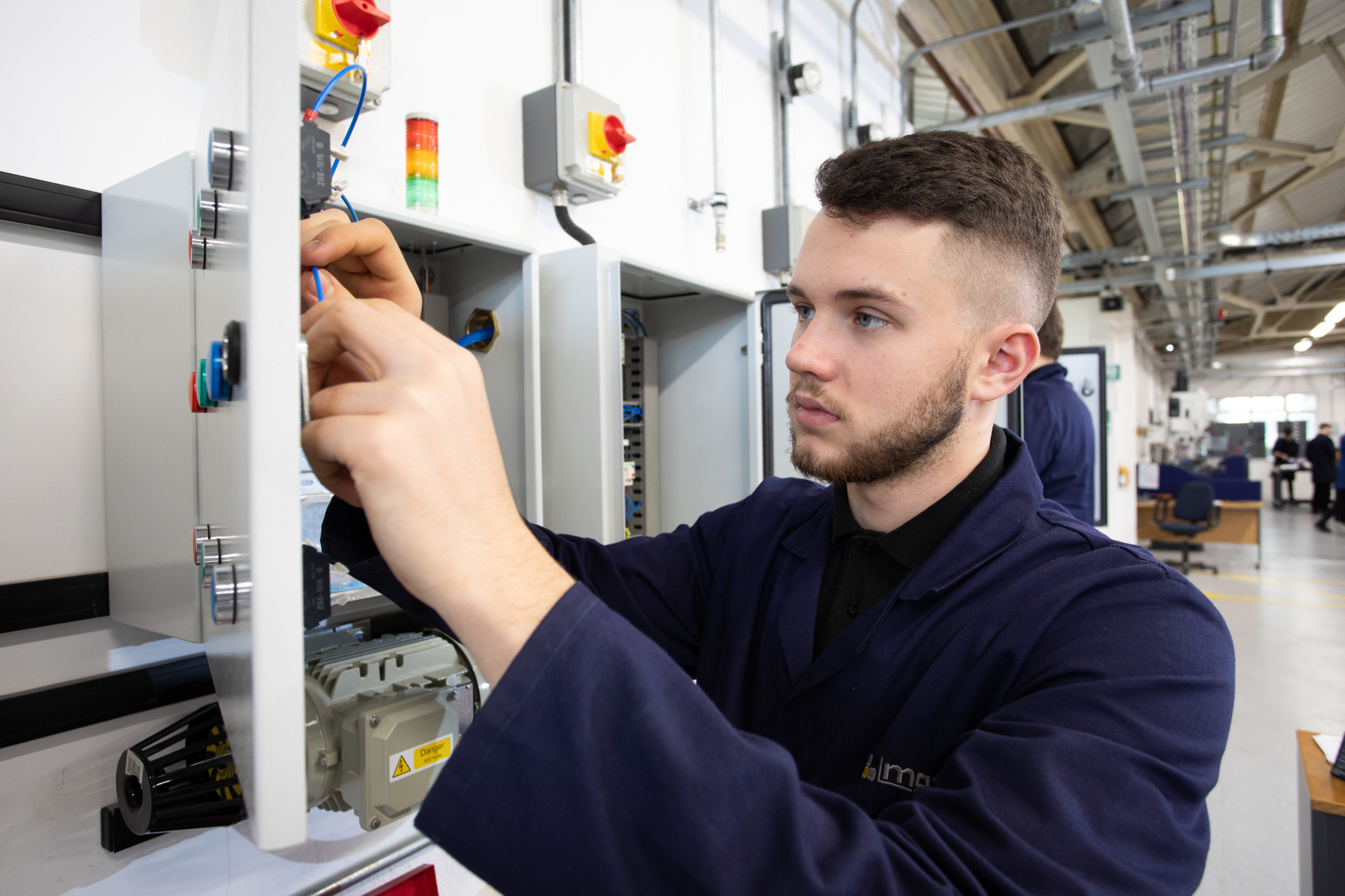 Engineering apprentice working on electrical installation