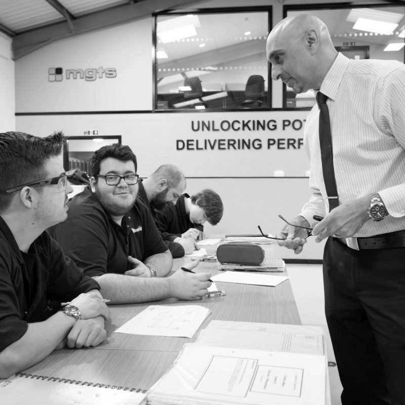 Male mentor helping engineering apprentices with coursework