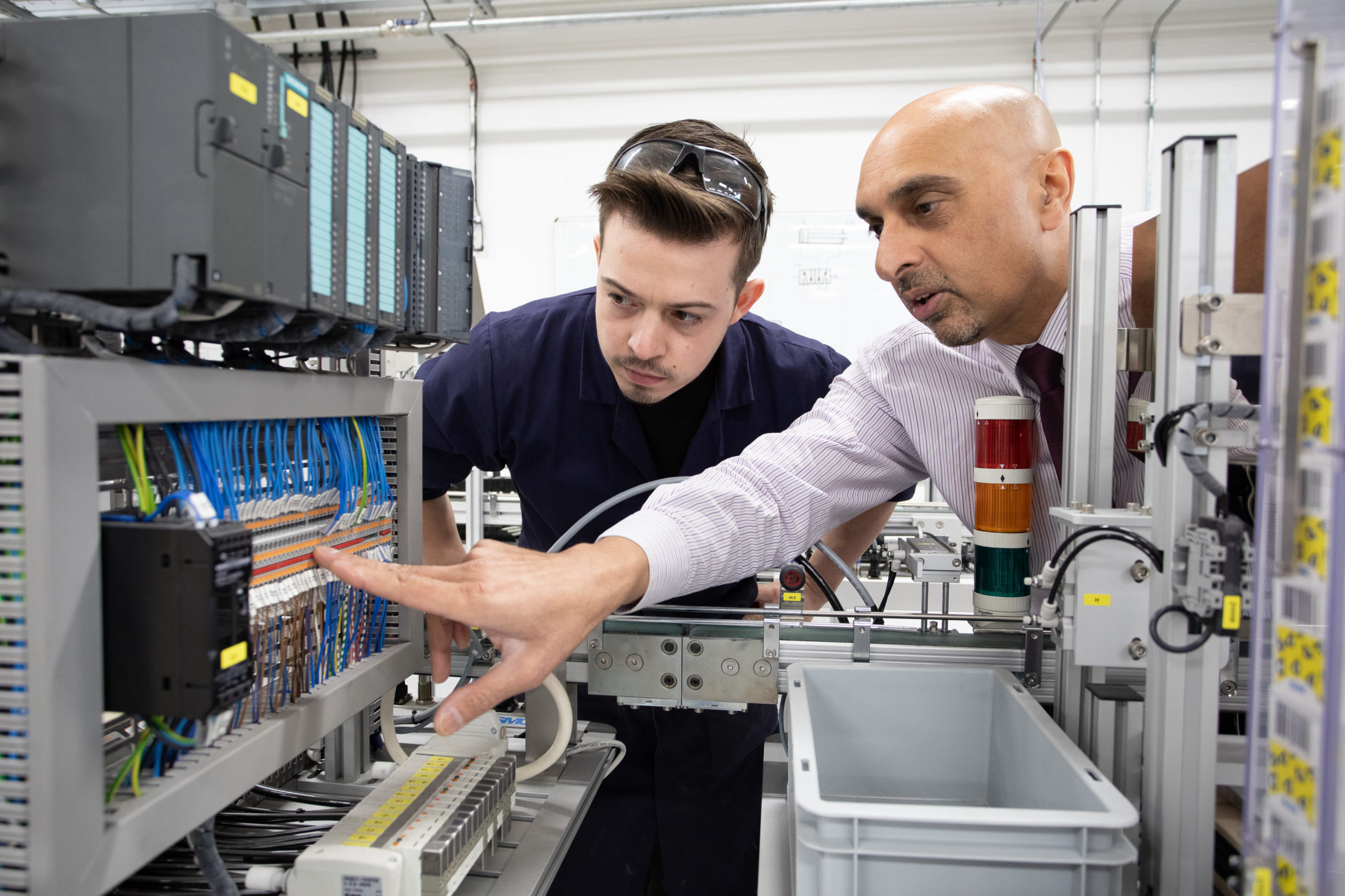 Male mentor speaking to Food and Drink Engineering Maintenance Technician apprentice about Automation fault finding