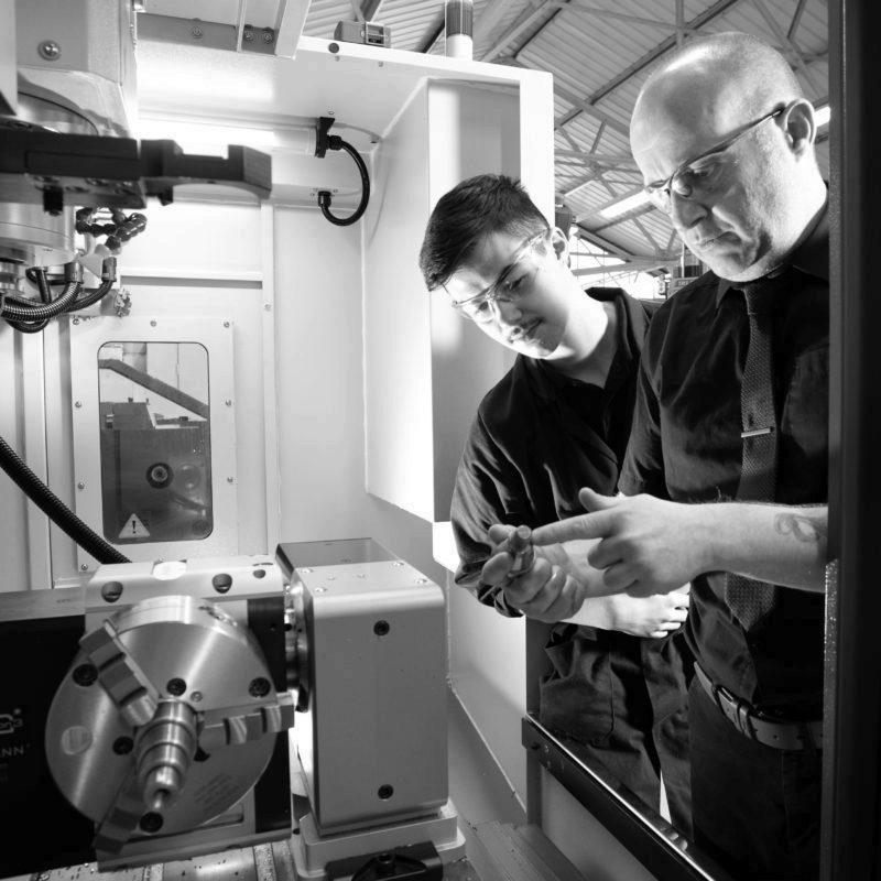Male mentor helping Machinist apprentice use CNC machine