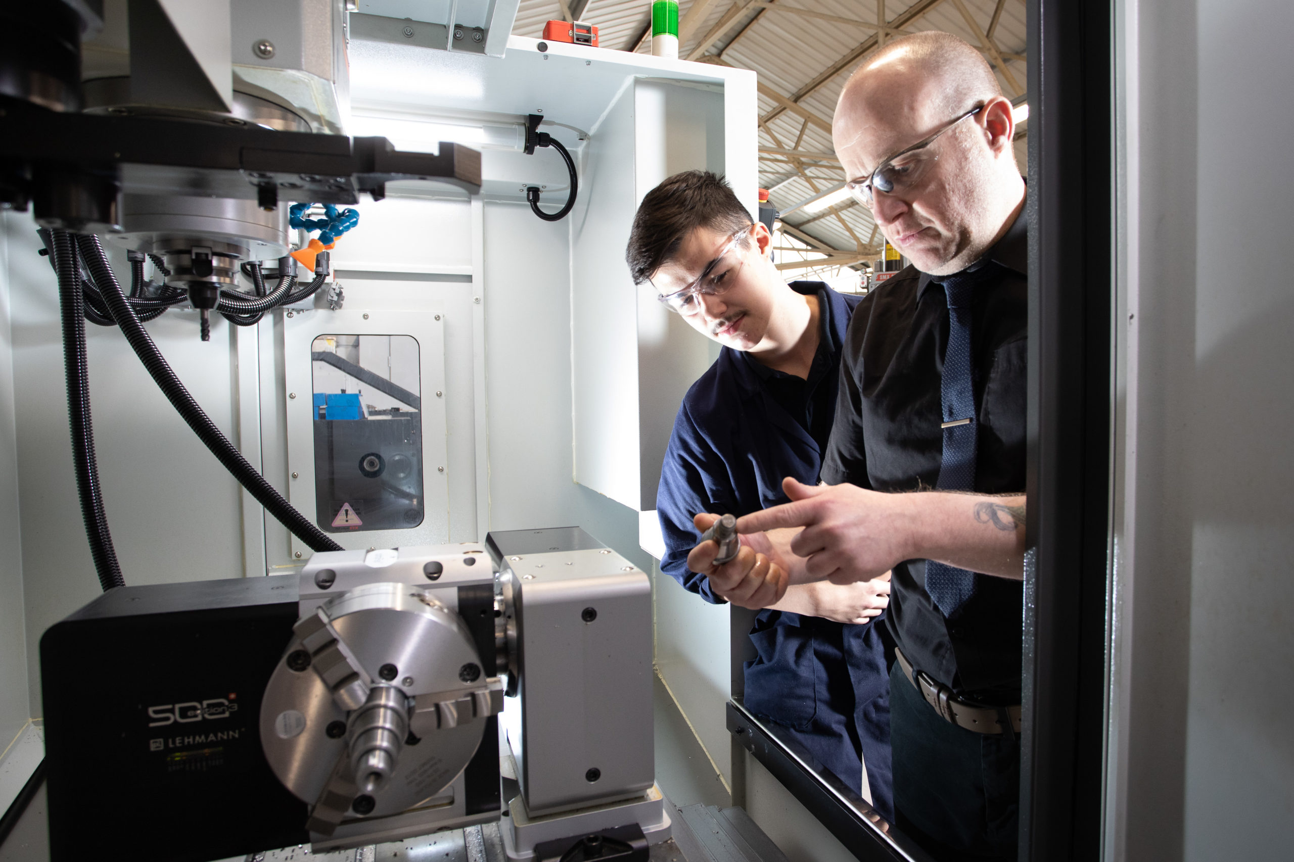 Male mentor helping Machinist apprentice use CNC machine