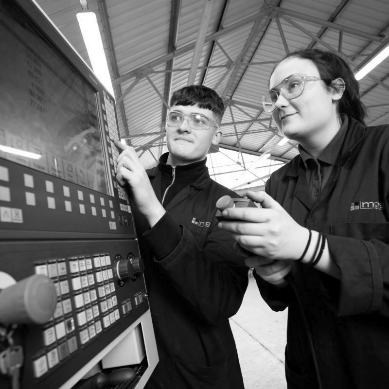 Two engineering apprentices using CNC machine