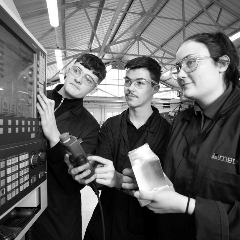 3 apprentices using machinery