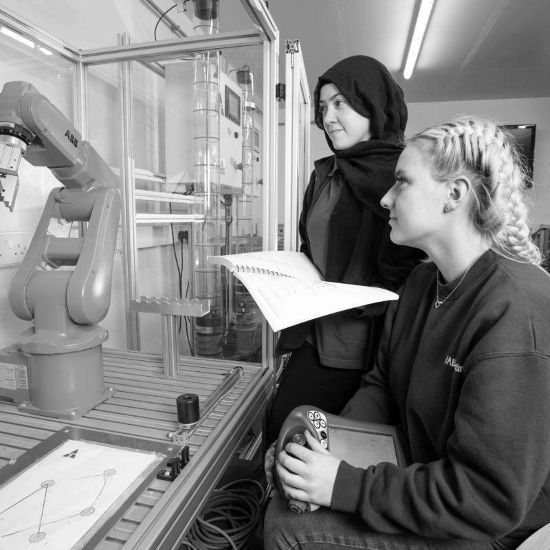 Two female Mechatronics maintenance technician apprentices learning robotics programming