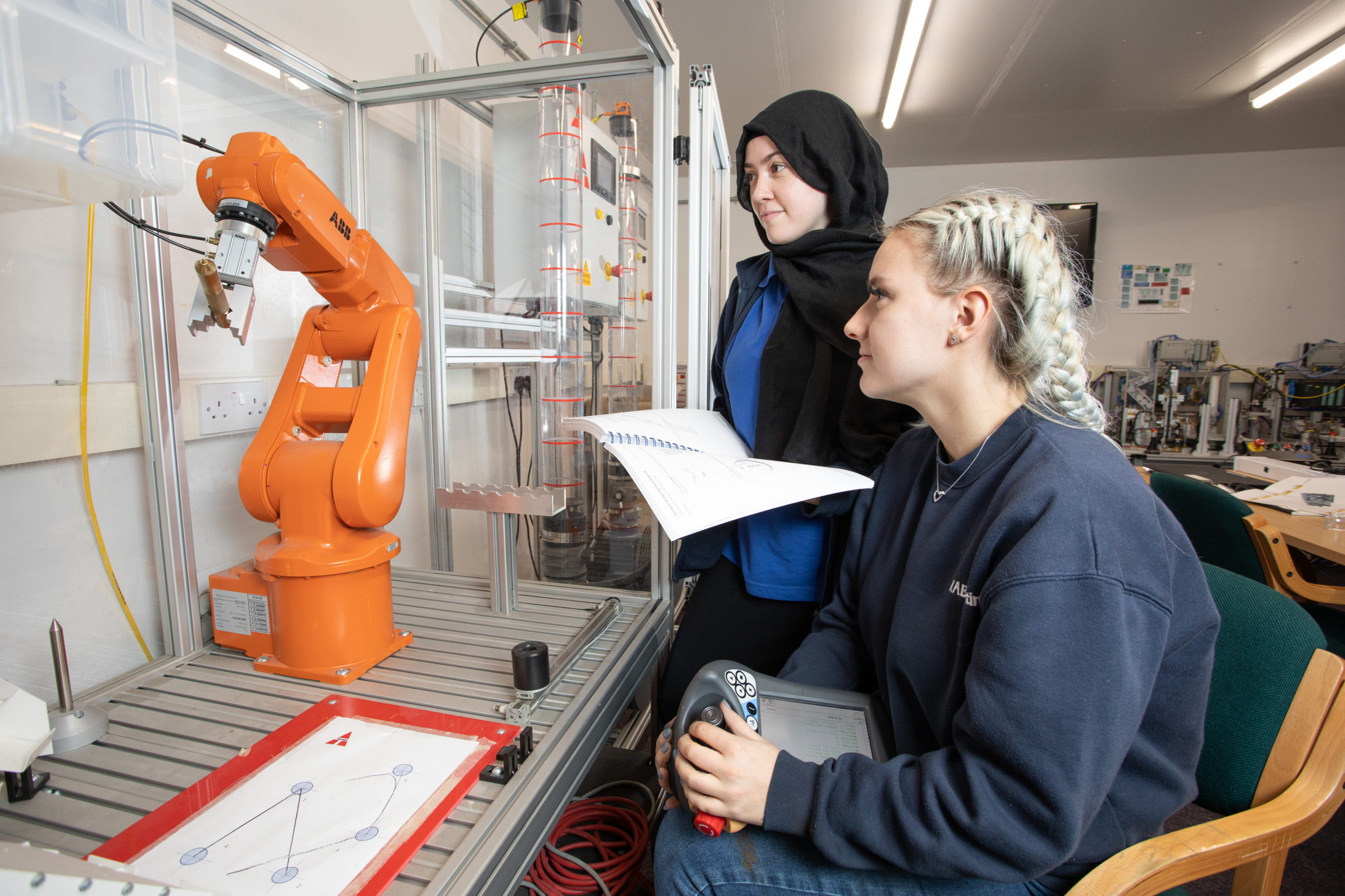 Two female Mechatronics maintenance technician apprentices learning robotics programming